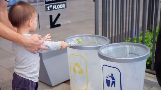 Cute little girls being taught how to recycle plastic bottles by her father