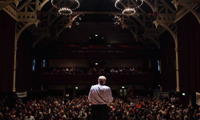 Jeremy Corbyn before audience in large hall