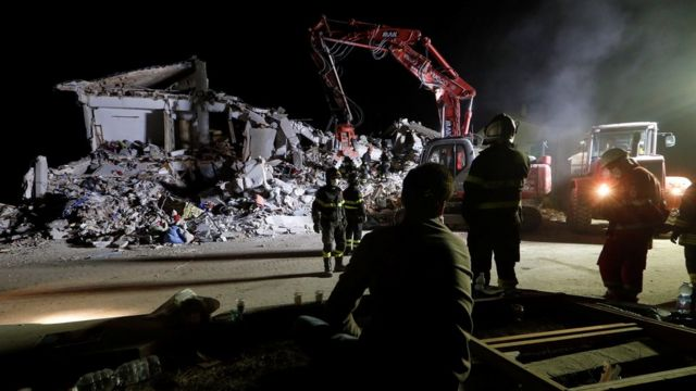 Firefighters work in the night at a collapsed house following an earthquake in Amatrice