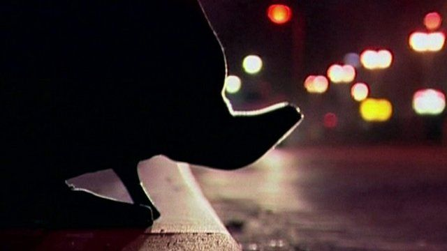 Prostitute's high-heel shoe on curb