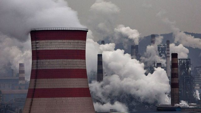 Smoke billows from smokestacks and a coal fired generator at a steel factory