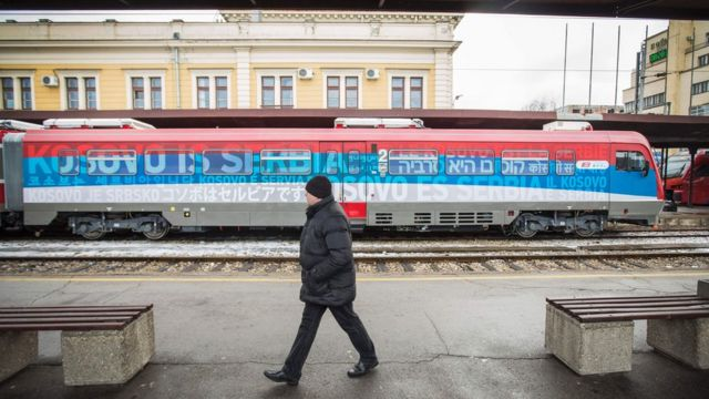 """A man passes a train decorated with the Serbian flag and the words """"Kosovo is Serbia"""" in Belgrade."""