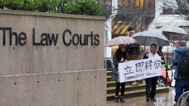在法庭外有人打出横幅支持孟晚舟。
