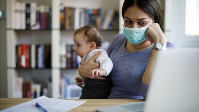 Mulher de máscara com bebê no colo, sentada em frente a mesa com laptop