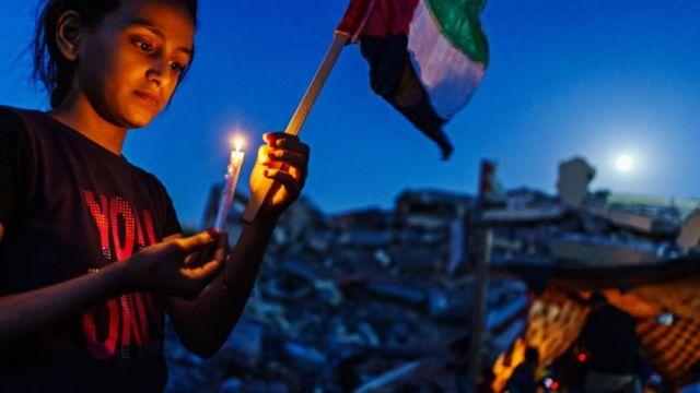 GAZA CITY, PALESTINIAN TERRITORY -- MAY 25, 2021: A young Palestinian girl lights a candle during a candlelighchildren t vigil to condemn the killing of and civilians, which is held over the rubble of homes destroyed by Israeli military strike during the 11-day escalation between Israel and Gaza military factions, which has now ended after an Egyptian-brokered ceasefire, bringing a momentary peace and calm to grieve and recover what was lost in Gaza City, Tuesday, May 25, 2021. In the same rubble, members of the Al-Madhoun family were killed ( Abdul Rahim Mohammed Madhoun (63) and his wife: Haijar Abu Sharkh al-Madhoun (60), and members of the al- al-Tanani family Ñ wife, husband and four children, were killed in an Israeli airstrike hit their houses in the dawn of the first day of Eid, on 13 May 2021, in addition to 7 family members of Al-Malfouh family were rescued from under the rubble of the same strike. 248 Palestinians were killed during this escalation, including 66 children. Eg