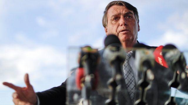 Bolsonaro dá entrevista em área externa, com vários microfones no palanque