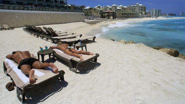 Turistas en una playa de Cancún.