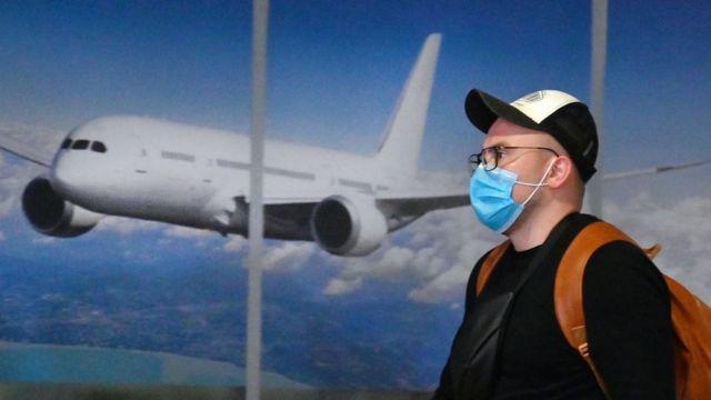 Hombre con mascarilla con un avión detrás.
