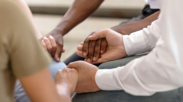 Três pessoas de mãos dadas em ritual religioso