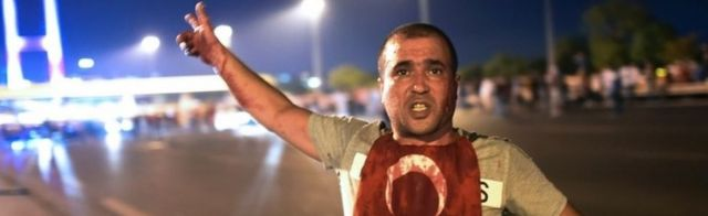 A Turkish man points to the Bosphorus bridge, July 2016
