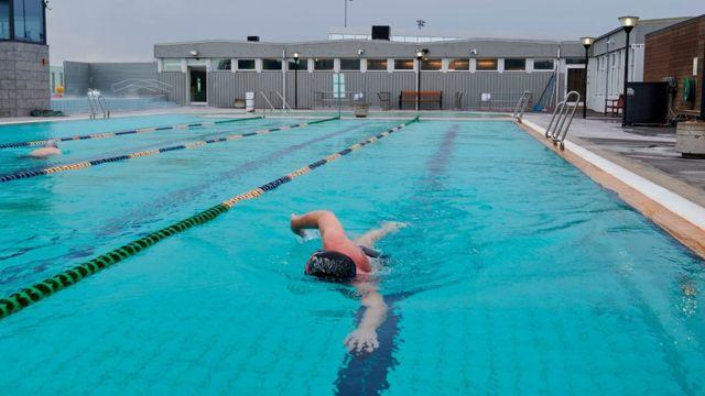 Homem nadando em piscina na Islândia