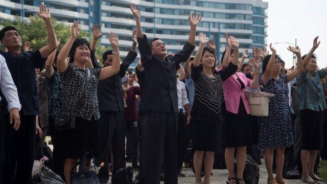 平壤民眾在街頭大電視屏幕前收看核試驗成功消息後集體舉手歡呼(3/9/2017)