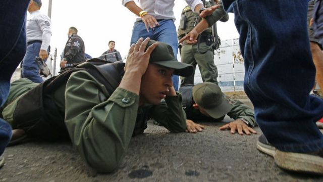 wo Venezuelan soldiers lie on the ground as they are detained by Colombian police