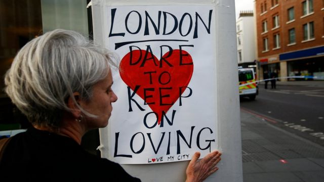 """A woman sticks a sign up saying: """"London dare to keep on loving"""""""