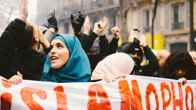 Mulher de lenço segura carta contra islamofobia em protesto na França em 2009