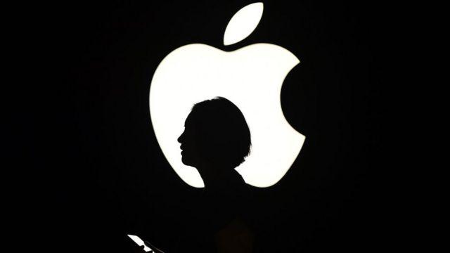la silueta de una mujer frente a un logo de Apple