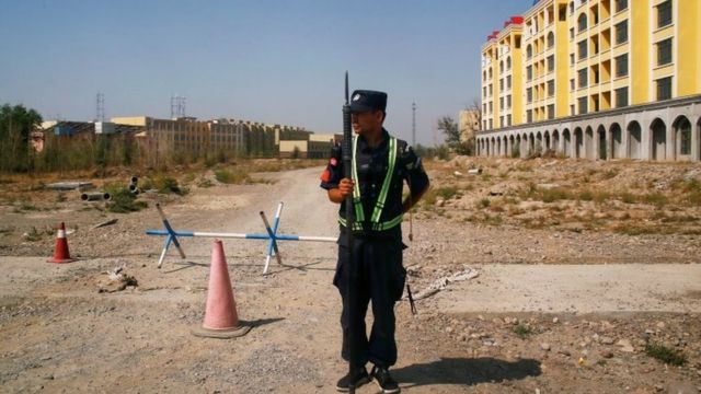 A police officer stands guard near a 'vocational education centre' in Xinjiang