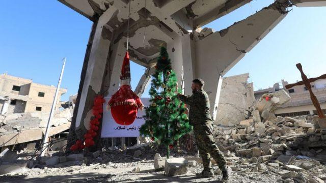 جندي يهيئ شجرة عيد الميلاد في سوريا