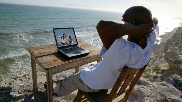 Hombre sentado con una computadora en la playa