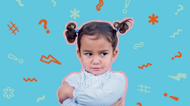A child with a serious expression and her arms crossed