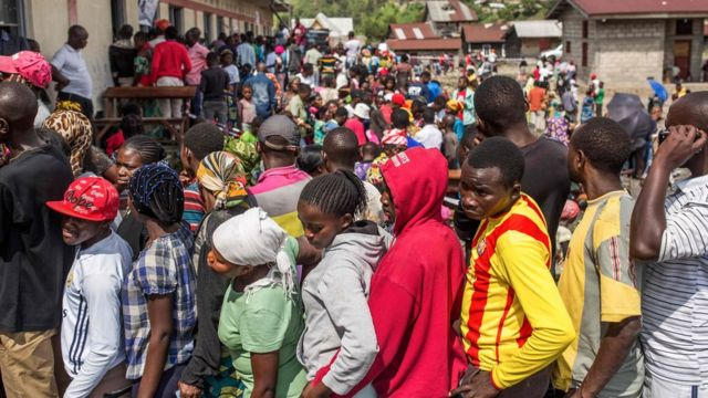 Voters wait in line to cast their ballot outside the Kibancha polling station in Sake, North Kivu, on December 30, 2018
