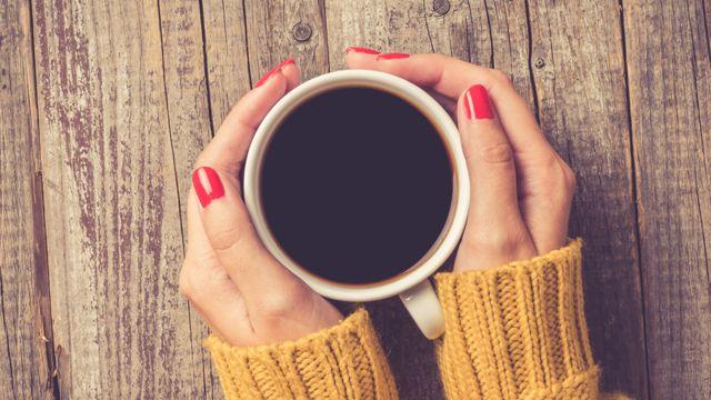 Manos de mujer en torno a una taza de café