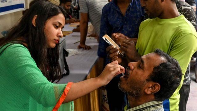 Un hombre recibe una vacuna por vía oral de una trabajadora de la salud en Daca, Bangladesh, febrero 2020