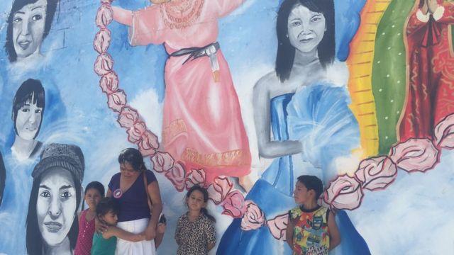 Anita Cuéllar con sus cuatro nietos junto al mural que mandó pintar con la imagen de su hija desaparecida.