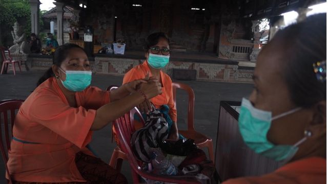 Petugas di Pura Batuan mengenakan masker untuk mengantisipasi penularan virus corona (30/01).