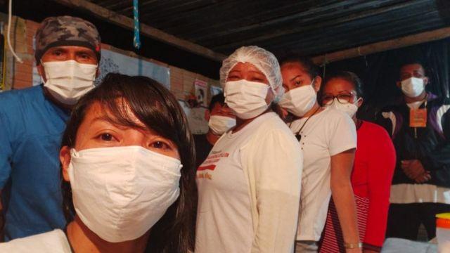 Vanda tira foto com outras seis pessoas de máscara, em ambiente interno
