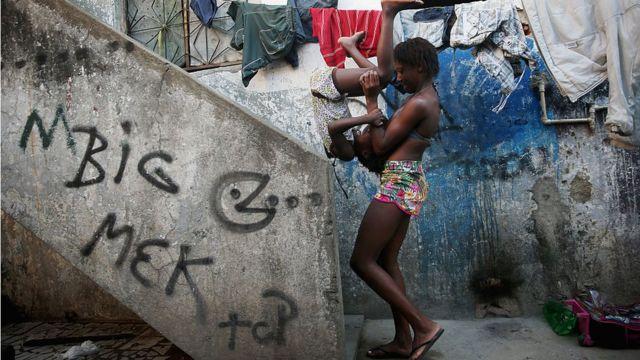 Mulher brinca com criança na Maré