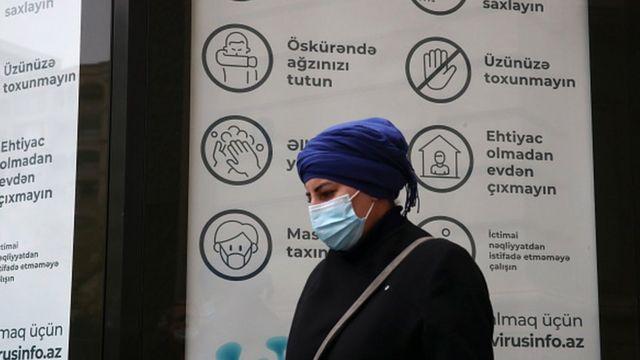 Üzü maskalı qadın koronavirus lövhəsi qarşısında