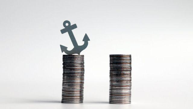 Ancla en miniatura sobre dos pilas de monedas.