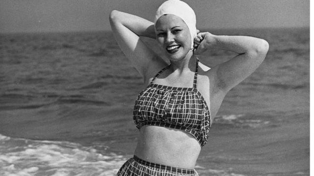 Девушка в скромном купальном костюме