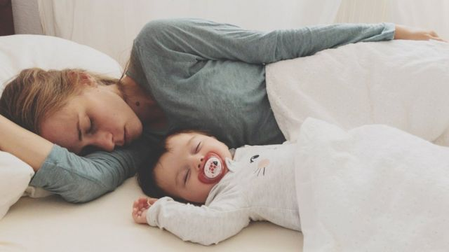 Mother And Son Sleeping On Bed At Home