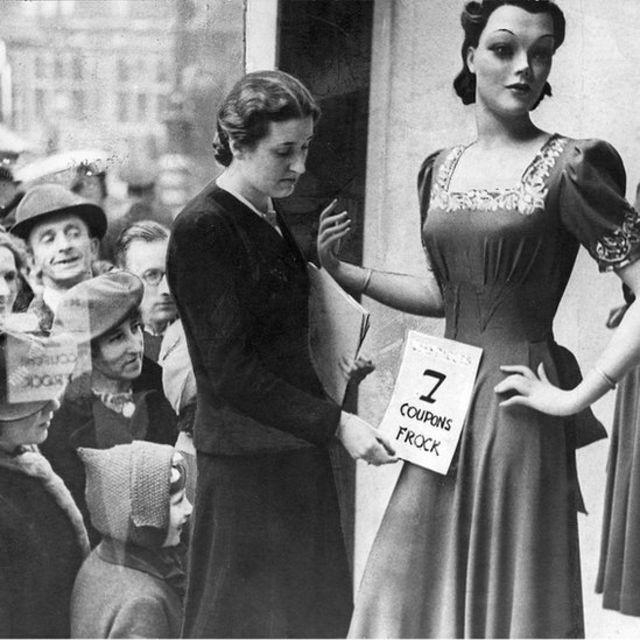Una mujer pone un cartel en un maniquí