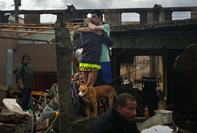 Residentes de Baracoa, Cuba, observan los daños causados por las lluvias y las penetraciones del mar.