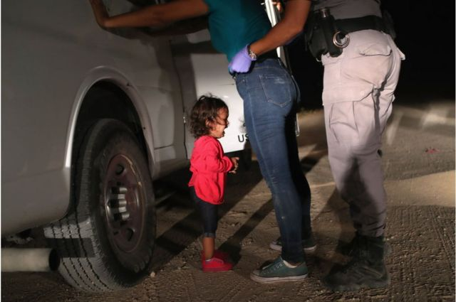 A two-year-old girl cries as her mother is searched and detained against a vehicle near the U.S.-Mexico border.
