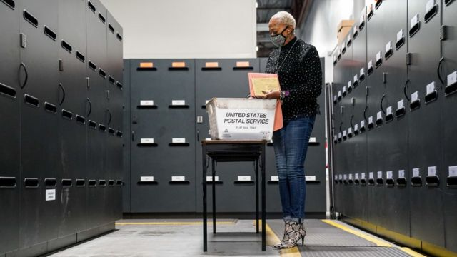 Una mujer rodeada de archivadores mirando a través de las papeletas en Georgia.
