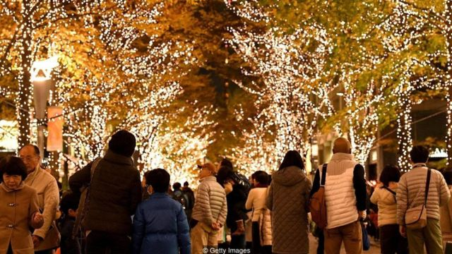 People walk beneath Christmas decorations in the Marunouchi shopping district of Tokyo on December 2, 2016
