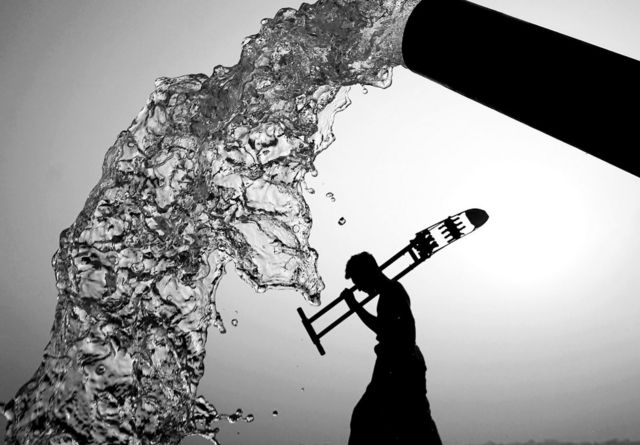 A black and white photo of a pipe gushing water with the silhouette of a man walking in the background