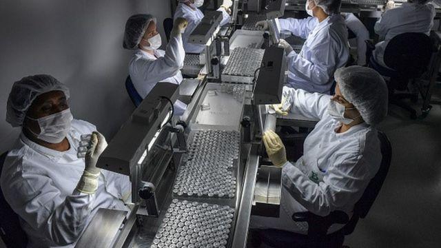 Linha de produção de vacina com profissionais usando equipamentos de proteção