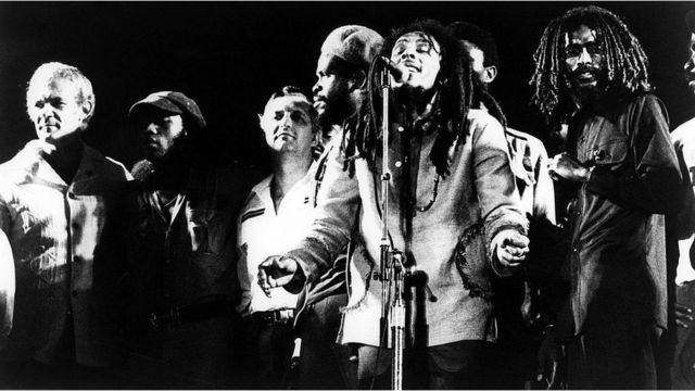 Bob Marley cantando al lado de su banda