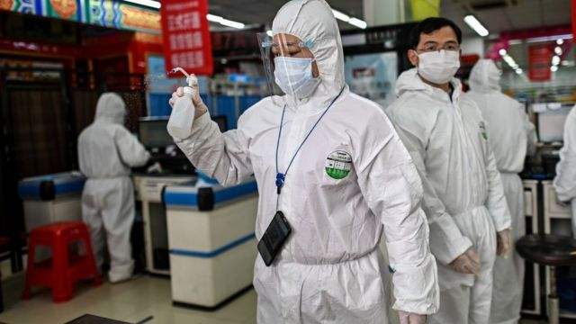 A woman wearing a protective suit sprays disinfectant in a pharmacy in Wuhan, in China's central Hubei province o­n March 30, 2020