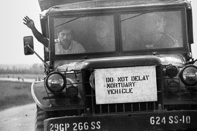 A sign on the front of a truck which reads 'do not delay mortuary vehicle'