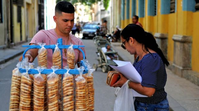Mulher compra biscoitos de um vendedor em Havana