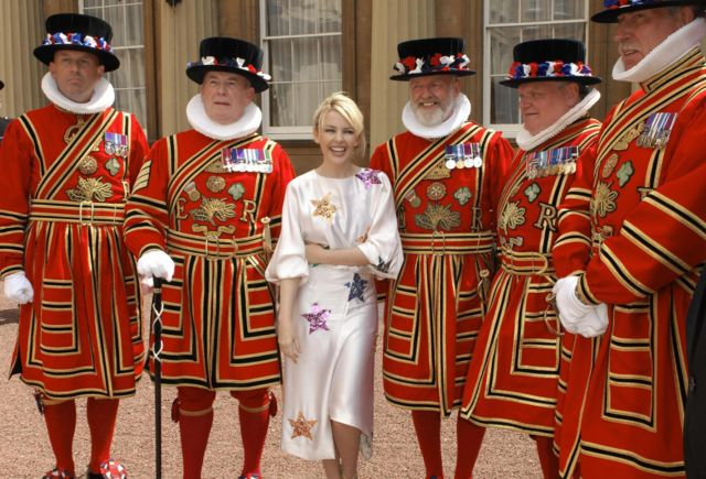 Australian pop singer Kylie Minogue (C) poses for photographs with Beefeaters after receiving her Order of the British Empire (OBE) from the Prince of Wales for services to music, at Buckingham Palace, in London, on 3 July 2008.