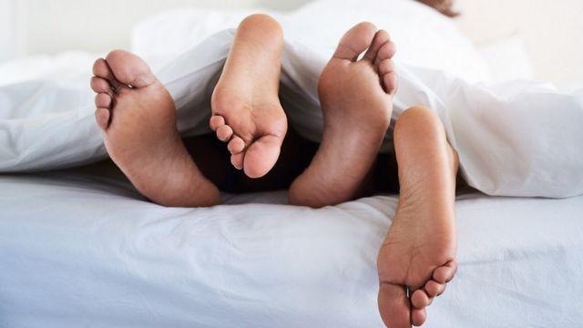 Vue des pieds d'un couple qui dépassent des draps.