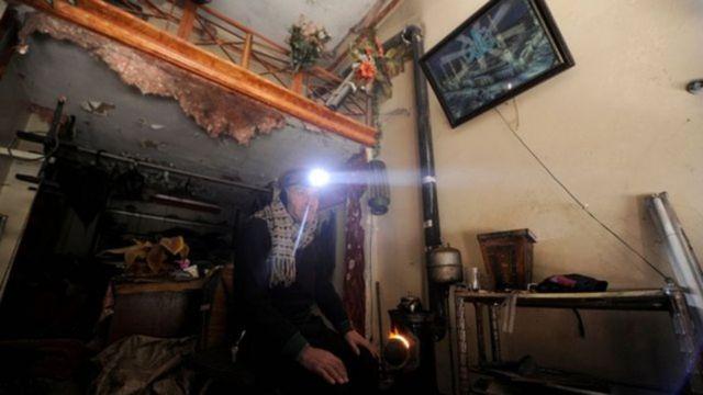 Hombre sentado en su casa abrigado con una linterna en Alepo, Siria.