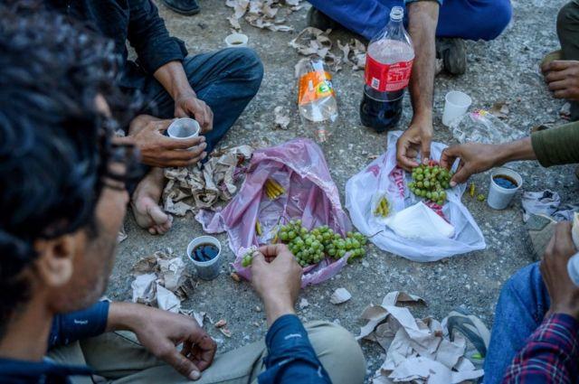 Yer sofrasında yemek yiyen göçmenler